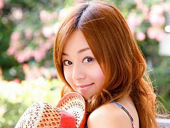 Red headed asian cutie posing in a floral printed...