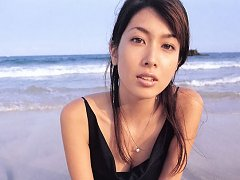 Sexy asian temptress laying around on the beach in...